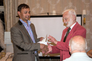 Vice President of the Peterborough Nepali Society presents Arthur with a cheque for £500